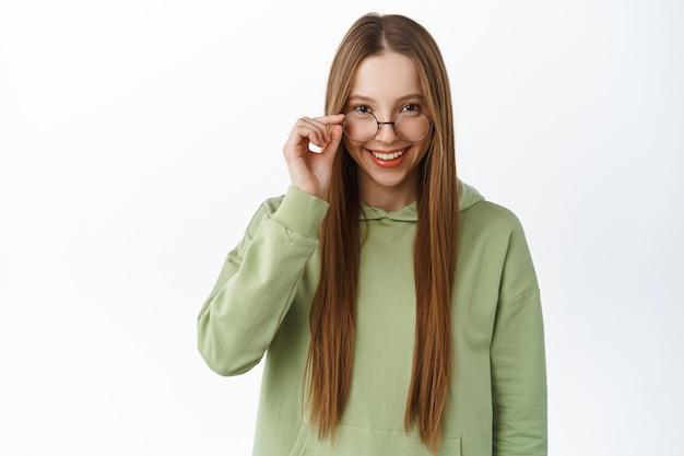 Uśmiechnięta studentka z długimi włosami, zdejmowanymi okularami i spojrzeniem z przodu, przymierzająca nowe okulary, stojąca w bluzie z kapturem na białej ścianie