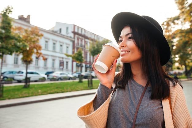 Uśmiechnięta stylowa młoda kobieta pije kawę