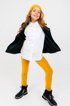 Uśmiechnięta stylowa, urocza uczennica w białej koszuli, rozpiętej czarnej skórzanej kurtce, z żółtą czapką na głowie, pozowanie na białym