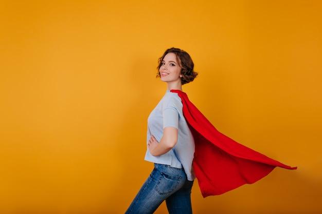 Uśmiechnięta supergirl w dżinsach stojących w pewnej pozie na żółtej przestrzeni