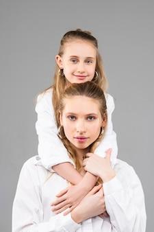 Uśmiechnięta, sympatyczna mała dziewczynka o niebieskich oczach, wsparta na swojej starszej siostrze, stojąc z tyłu podczas sesji zdjęciowej photo