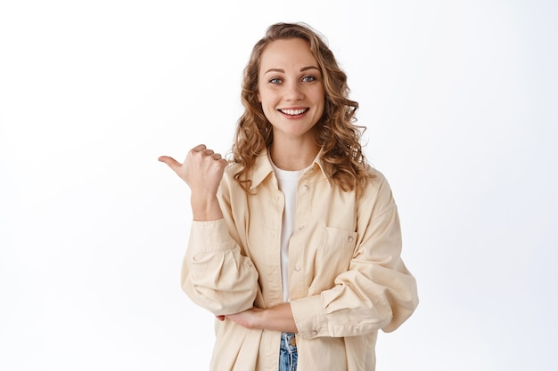 Uśmiechnięta szczera dziewczyna z blond kręconymi włosami, wskazująca kciukiem po lewej stronie, pokazująca reklamę, dająca rekomendację, stojąca nad białą ścianą