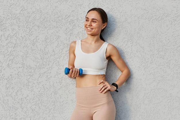 Uśmiechnięta szczęśliwa atrakcyjna ciemnowłosa kobieta w młodym wieku, ubrana w biały top i beżowe legginsy, trzymająca hantle w rękach, wykonująca ćwiczenia sportowe na biceps i triceps.