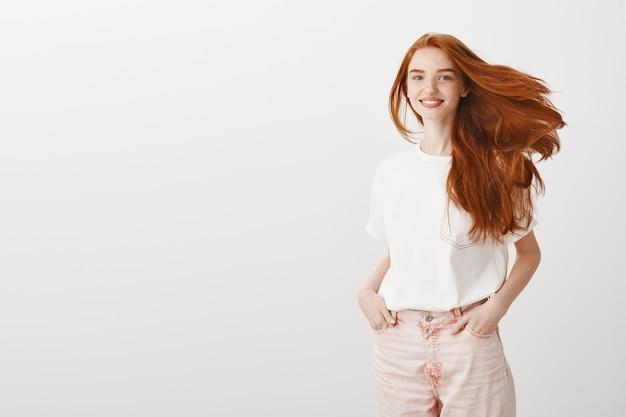 Uśmiechnięta szczęśliwa, atrakcyjna ruda dziewczyna kręci głową i cieszy się nową fryzurą