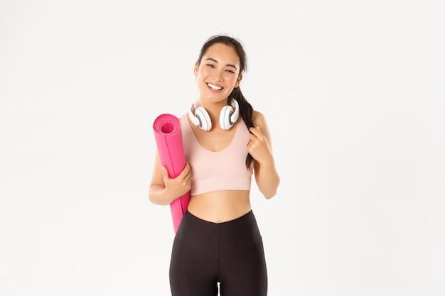 Uśmiechnięta szczęśliwa azjatycka dziewczyna fitness w słuchawkach i odzieży sportowej, nosić gumową matę do treningu lub jogi, śmiejąc się beztrosko na białym tle.