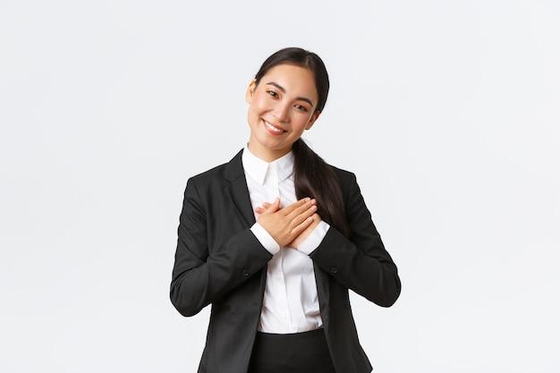 Uśmiechnięta szczęśliwa azjatycka przedsiębiorczyni otrzymuje pochwały lub komplementy, trzymając ręce na sercu, uśmiechając się i wyglądając na pochlebną, czując się wdzięczna, stojąc zachwycona białym tłem