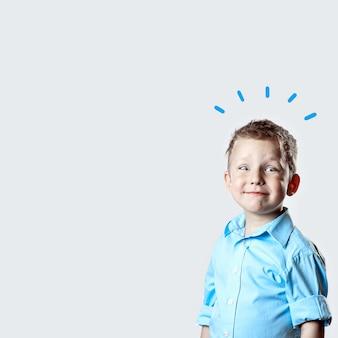 Uśmiechnięta szczęśliwa chłopiec w błękitnej koszula na lekkim tle