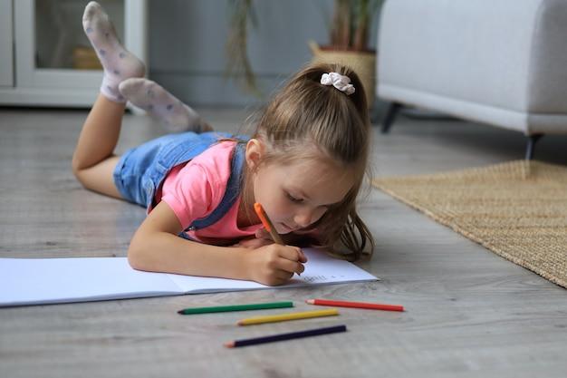 Uśmiechnięta szczęśliwa dziewczyna leżąca na ciepłej podłodze z zabawkowym słoniem obok niej, ciesząca się twórczą aktywnością, rysująca ołówki, kolorując zdjęcia w albumach.
