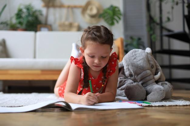 Uśmiechnięta szczęśliwa dziewczyna leżąca na ciepłej podłodze z zabawkowym słoniem obok niej, ciesząca się twórczą aktywnością, rysująca ołówkiem, kolorująca zdjęcia w albumach