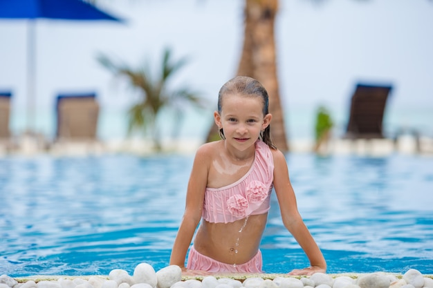 Uśmiechnięta szczęśliwa dziewczyna ma zabawę w plenerowym pływackim basenie