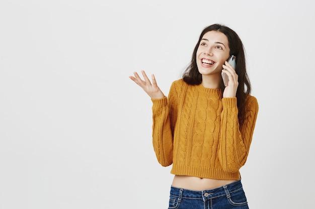 Uśmiechnięta szczęśliwa dziewczyna opowiada na telefonie komórkowym