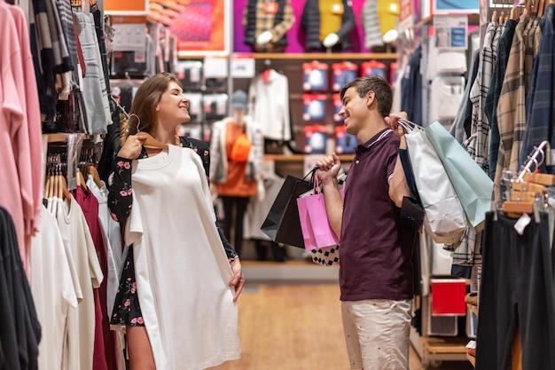 Uśmiechnięta, szczęśliwa dziewczyna przymierza sukienkę, którą naprawdę lubiła, a facet patrzy na nią z aprobatą,