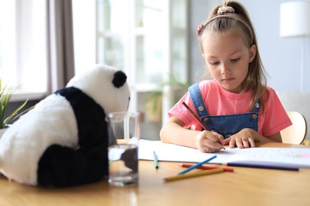 Uśmiechnięta szczęśliwa dziewczyna siedzi przy stole z misiem pandą obok niej, ciesząc się aktywnością twórczą, rysując ołówki, kolorując zdjęcia w albumach.