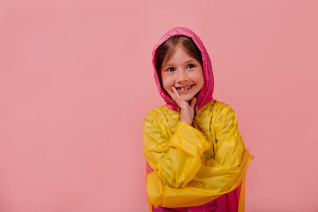 Uśmiechnięta szczęśliwa dziewczyna ubrana w jasny płaszcz przeciwdeszczowy, uśmiechając się i trzymając rękę w pobliżu twarzy