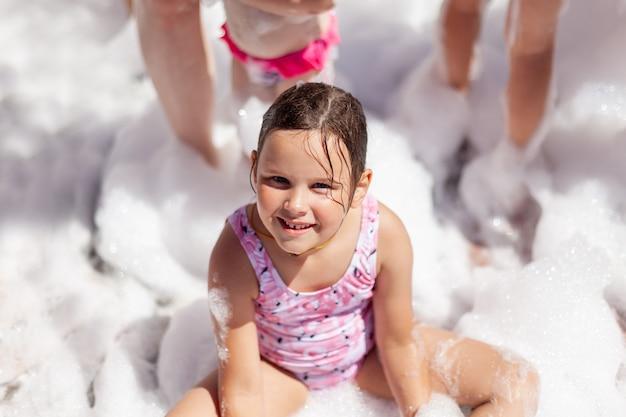 Uśmiechnięta szczęśliwa dziewczyna w różowym stroju kąpielowym siedzi przy basenie na imprezie z pianką w hotelu na s...