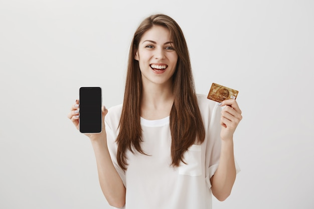 Uśmiechnięta szczęśliwa kobieta pokazuje wyświetlacz telefonu komórkowego i kartę kredytową. promocja aplikacji do zakupów