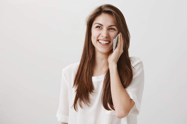 Uśmiechnięta szczęśliwa kobieta rozmawia przez telefon, dzwoniąc do kogoś