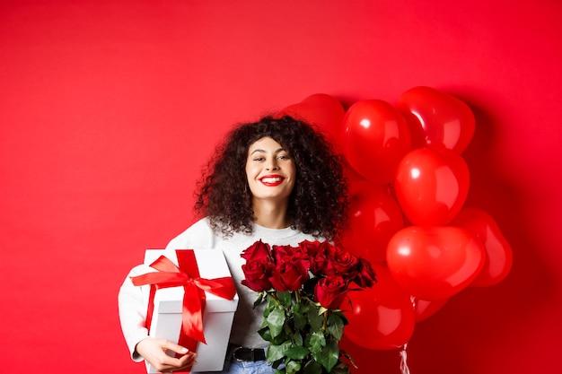 Uśmiechnięta szczęśliwa kobieta trzyma pudełko z prezentem i czerwonymi różami od chłopaka, świętuje walentynki, stojąc w pobliżu balonów romantycznych serc, stojąc na tle studia.