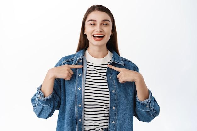 Uśmiechnięta szczęśliwa kobieta wybierana, wskazująca na siebie, promująca się, potrzebujesz mnie gest, wolontariat, chce uczestniczyć, stojąc nad białą ścianą