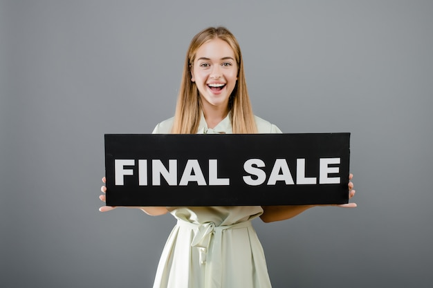 Uśmiechnięta szczęśliwa kobieta z definitywnym sprzedaż znakiem odizolowywającym nad popielatym
