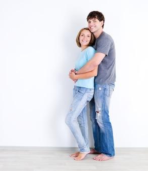 Uśmiechnięta szczęśliwa kochająca para w dorywczo stojących w pustym pokoju - w pomieszczeniu