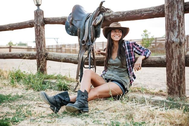 Uśmiechnięta szczęśliwa kowbojka w kapeluszu siedzi i odpoczywa na ogrodzeniu rancza