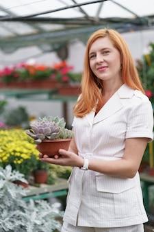 Uśmiechnięta szczęśliwa kwiaciarka w swoim przedszkolu stojąca, trzymając w rękach doniczkową kombinację sukulentów, gdy zajmuje się roślinami ogrodowymi w szklarni