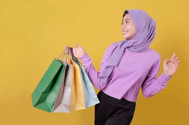 Uśmiechnięta szczęśliwa ładna dziewczyna za pomocą telefonu komórkowego, zakupy online, przynieś torbę, wesoła i radosna