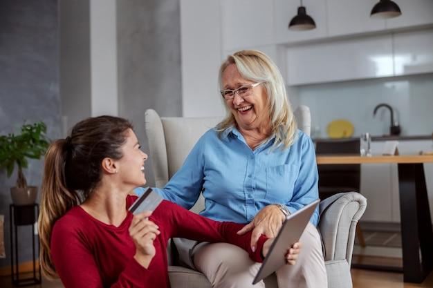 Uśmiechnięta szczęśliwa matka i córka zakupy online.