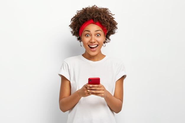 Uśmiechnięta, szczęśliwa młoda kobieta trzyma nowoczesny telefon komórkowy, uśmiecha się pozytywnie, surfuje po internecie, tworzy własnego bloga, nosi białą koszulkę