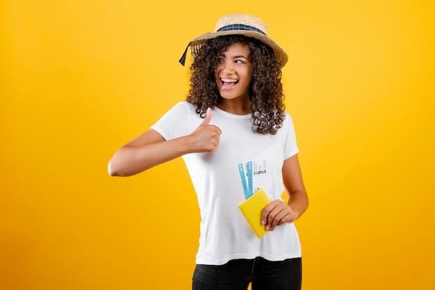 Uśmiechnięta szczęśliwa murzynka jest ubranym kapelusz odizolowywającego nad kolorem żółtym z biletami