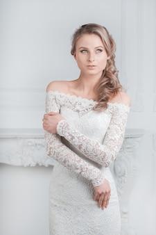 Uśmiechnięta szczęśliwa panna młoda przymierza suknię ślubną. święta i imprezy