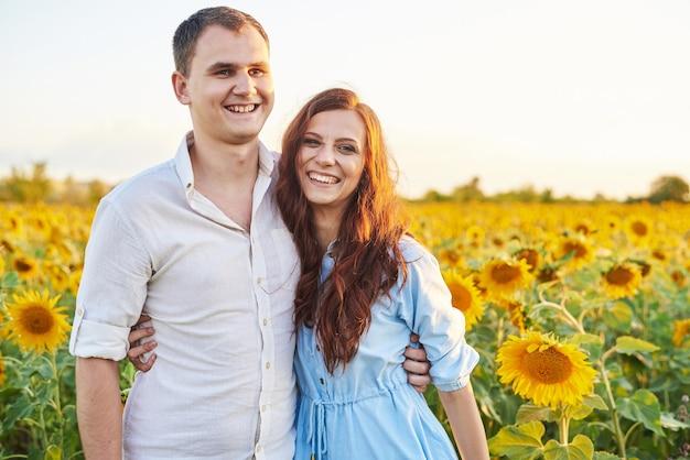 Uśmiechnięta szczęśliwa para nowożeńców w polu słoneczników