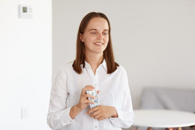 Uśmiechnięta szczęśliwa piękna kobieta o ciemnych włosach, ubrana w białą koszulę w stylu casual, trzymająca pieniądze w rękach, odwracająca wzrok z pozytywnym wyrazem twarzy, pozująca w jasnym pokoju w domu.