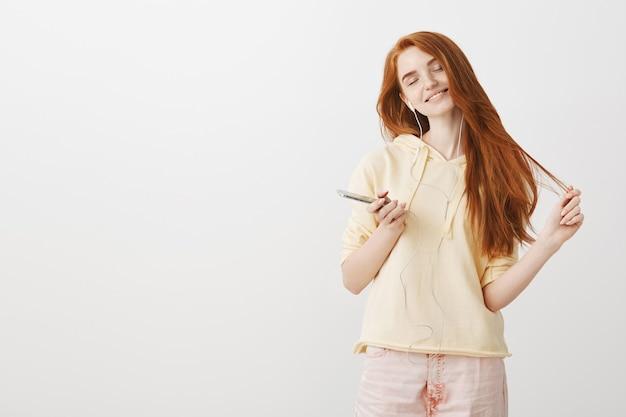 Uśmiechnięta szczęśliwa ruda dziewczyna zamyka oczy, aby cieszyć się muzyką w słuchawkach, trzymając telefon komórkowy