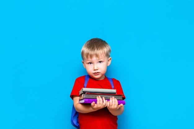 Uśmiechnięta szczęśliwa śliczna mądra chłopiec z plecakiem. dziecko z stosem książek w jego rękach. gotowy do szkoły. powrót do szkoły
