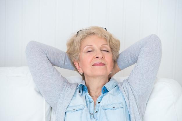 Uśmiechnięta szczęśliwa starsza kobieta relaksuje w domu