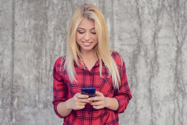 Uśmiechnięta szczęśliwa wesoła kobieta z blond włosami, w kraciastej koszuli za pomocą telefonu komórkowego 3g, 4g interent do czatowania i wysyłania wiadomości.