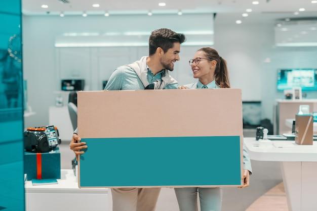 Uśmiechnięta szczęśliwa wielokulturowa para ubierał eleganckiego mienia pudełko z nowym osoczem tv i patrzeć each inny podczas gdy stojący w technika sklepie.