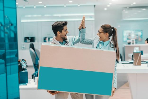 Uśmiechnięta szczęśliwa wielokulturowa para ubierał eleganckiego mienia pudełko z nowym telewizorem plazmowym i daje piątce each inny podczas gdy stojący w technika sklepie.