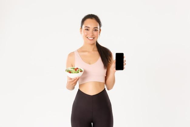 Uśmiechnięta szczupła i urocza azjatycka dziewczyna fitness, trener siłowni pokazująca sałatkę i ekran smartfona, polecam pobranie trackera diety lub przypomnienia o kaloriach.