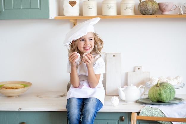 Uśmiechnięta szef kuchni dziewczyna bawić się w kuchni w domu