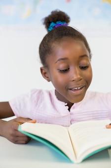 Uśmiechnięta szkolnej dziewczyny czytelnicza książka w sala lekcyjnej