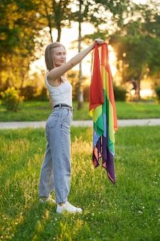 Uśmiechnięta tolerancyjna kobieta trzymająca tęczową flagę lgbt