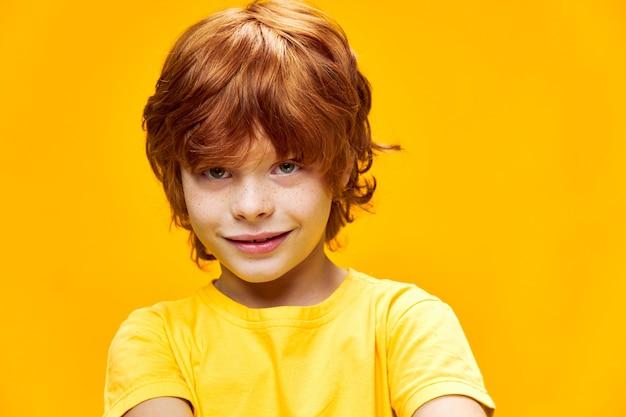 Uśmiechnięta twarz chłopca rude bliska studio żółta koszulka na białym tle