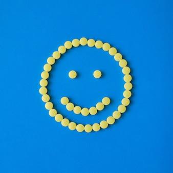 Uśmiechnięta twarz z żółtych okrągłych tabletek na niebieskim tle. tabletki, pigułki, witaminy, koncepcja medycyny.
