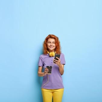 Uśmiechnięta tysiącletnia kobieta z falistymi rudymi włosami, pozująca do błękitnej ściany