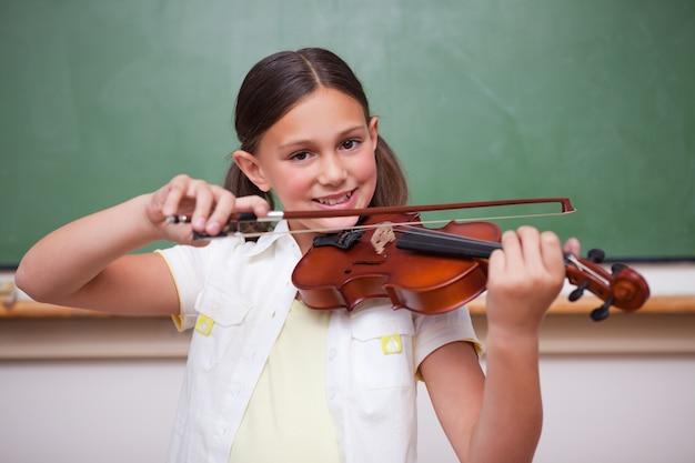 Uśmiechnięta uczennica gra na skrzypcach