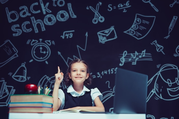 Uśmiechnięta uczennica podnosząca palec wskazujący do góry, siedząca z laptopem i książkami edukację na odległość