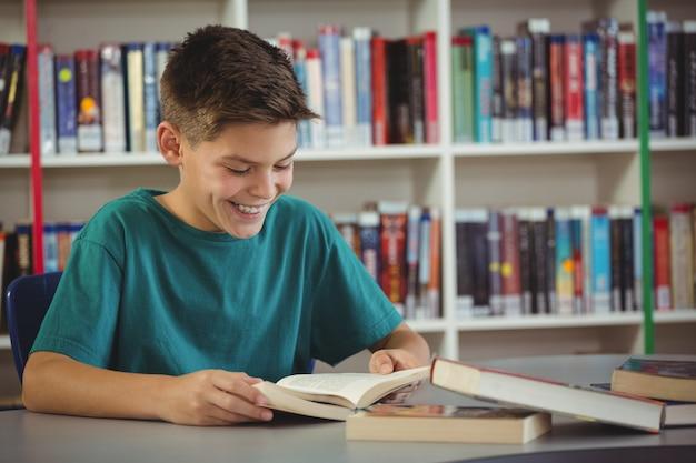 Uśmiechnięta uczniowska czytelnicza książka w bibliotece